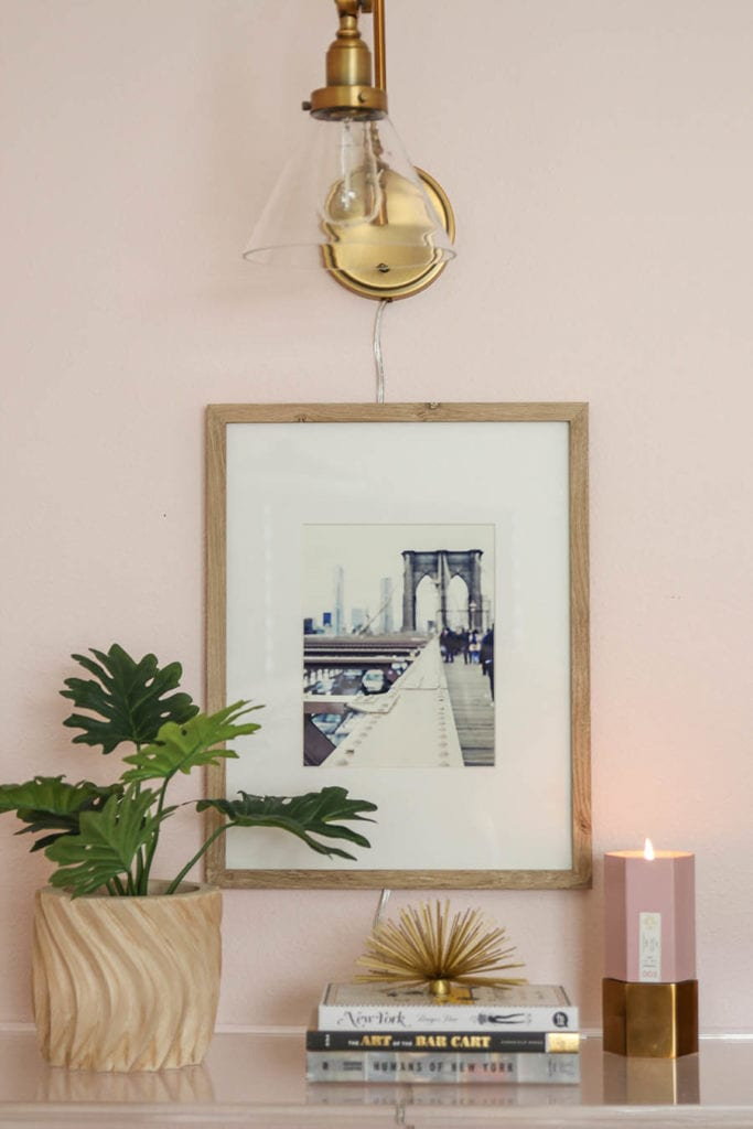 blush bedroom with art and gold lamp