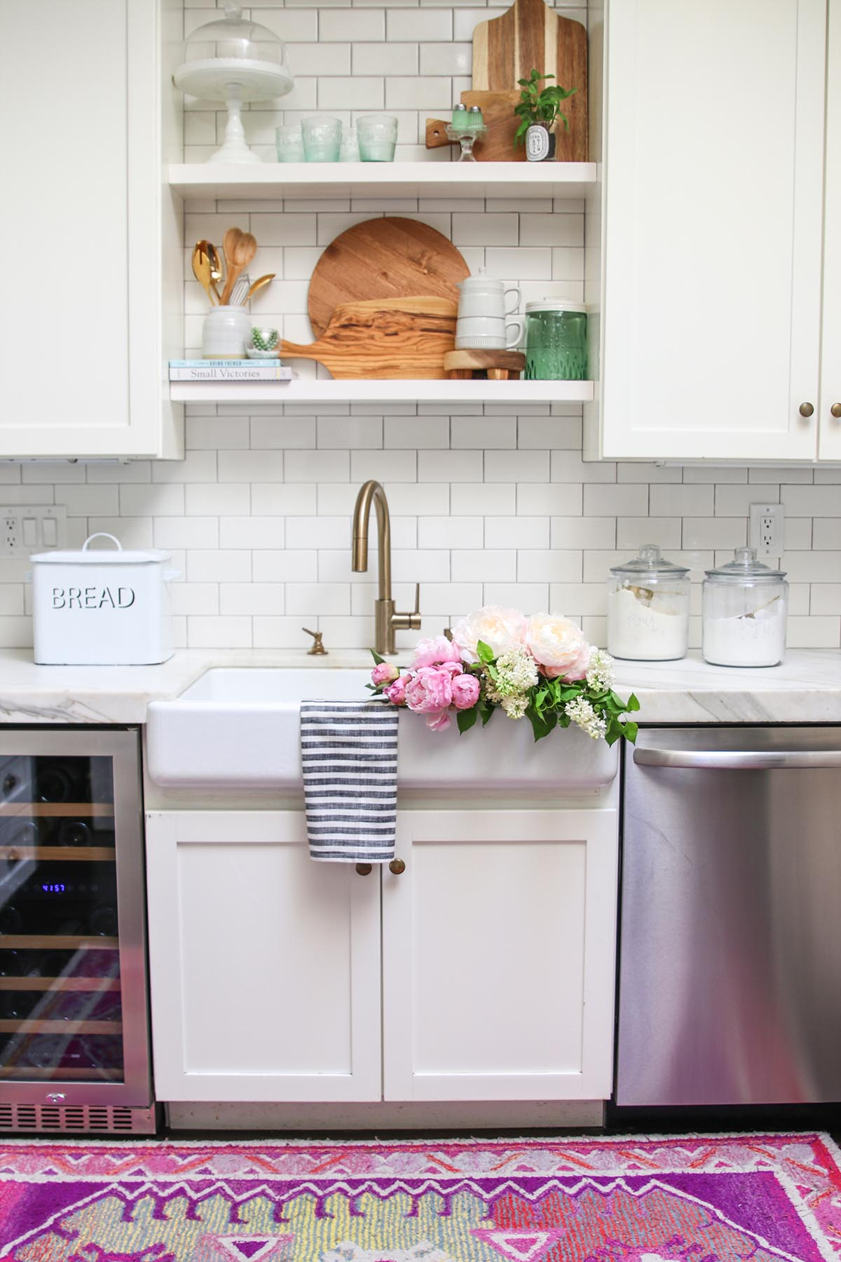 white kitchen with peonies in sink