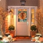 fall porch decorated with pumpkins and cornstalks