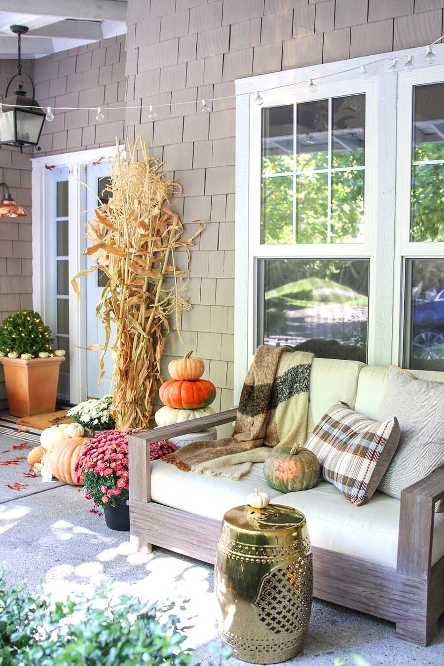 Neutral fall porch with pumpkins and cornstalks