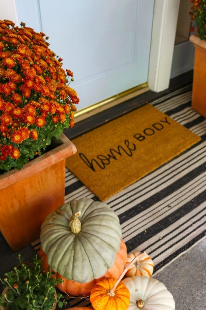 fall front doormat layered with pumpkins