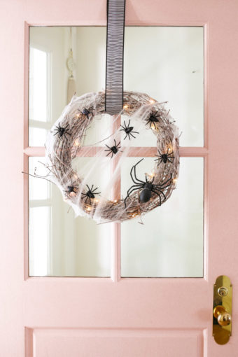 pink door with halloween wreath