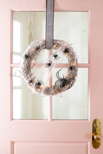 pink door with halloween wreath